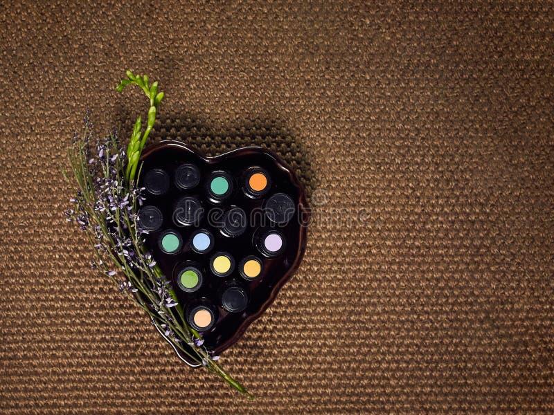 Die verschiedenen ätherischen Öle, abgefüllt in den kleinen Flaschen und in einer Herzform mit einer Lavendelniederlassung verein stockfotos