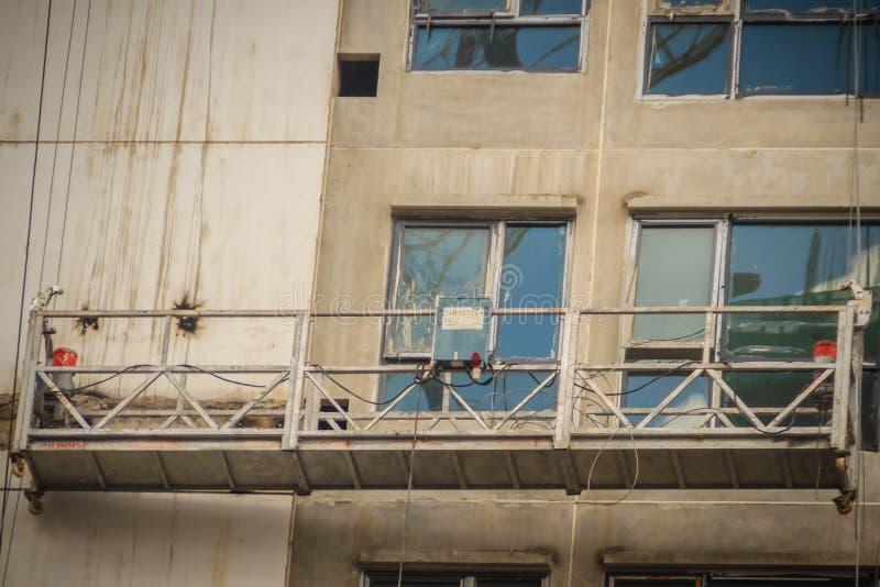 Die verschobene Wiege für Außenarbeit im HalloaufstiegsHochbau Die Gondelbahn oder das Stadiumsbaugerüst für externes repai stockbild