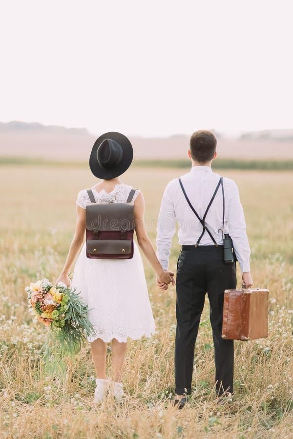 Die vertikale Ansicht der Rückseite der Jungvermählten, welche die Zeit auf dem sonnigen Gebiet genießen Die Braut hält stockbild