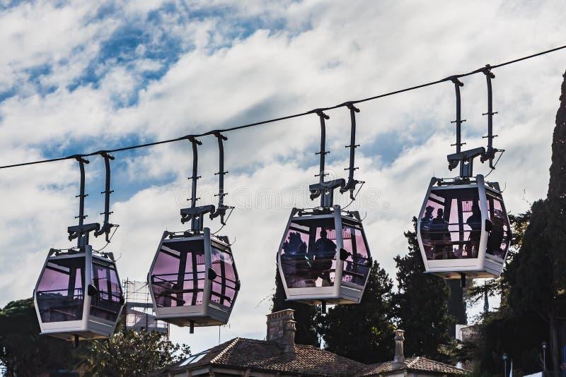 Die vier weißen Kabinen der Drahtseilbahnen mit transparenten Fenstern und Leuten unter braunen Dächern auf dem blauen Himmel mit stockfoto
