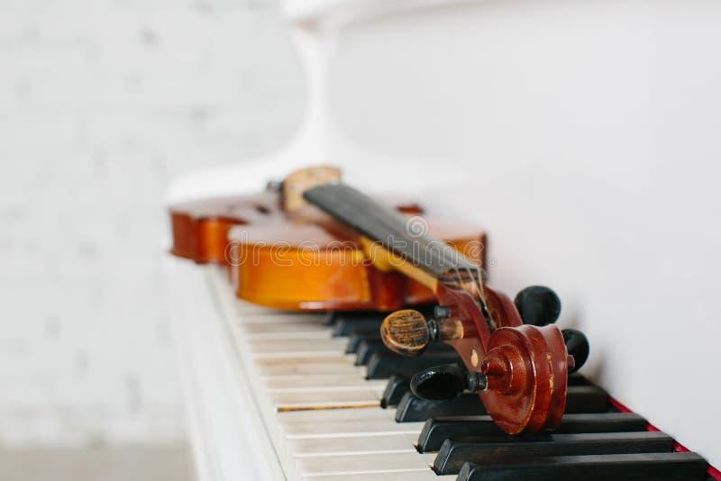 Die Violine und die Tastatur des weißen Klaviers stockbilder
