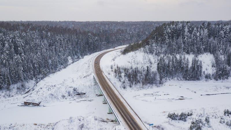 Die Vogelperspektive der Landstraße durchlaufend den schönen Schnee umfasste Landschaften stockfotografie