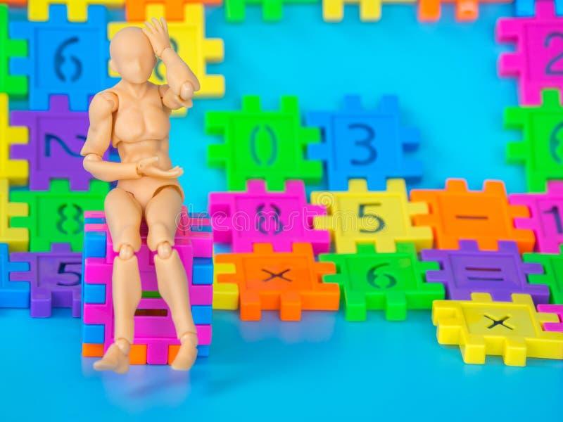 Die vorbildlichen Action-Figur-Plastikkopfschmerzen und das Sitzen auf Farbvollem Würfel machen von der Plastikzahl auf blauem Hi stockfotos