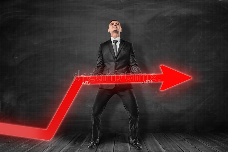 Die Vorderansicht des Geschäftsmannes und versuchend, roten Diagrammpfeil stehend nahe schwarzem Diagramm anzuheben ordnete Wand  stockfotos
