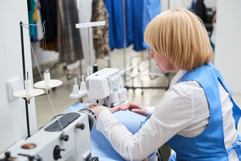 Die Wäschereiarbeitskraft führt Reparatur von Kleidung auf der Nähmaschine durch lizenzfreies stockbild