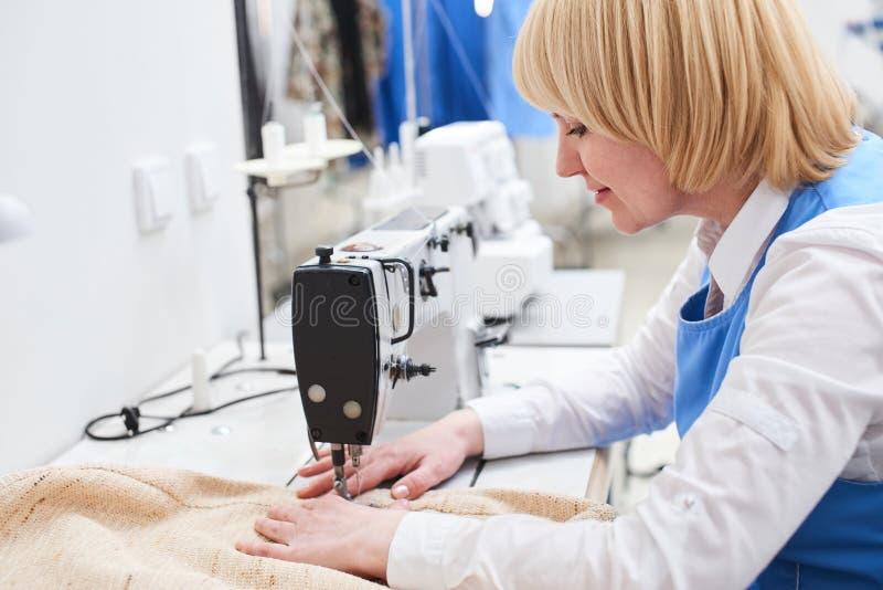 Die Wäschereiarbeitskraft führt Reparatur von Kleidung auf der Nähmaschine durch lizenzfreie stockfotos