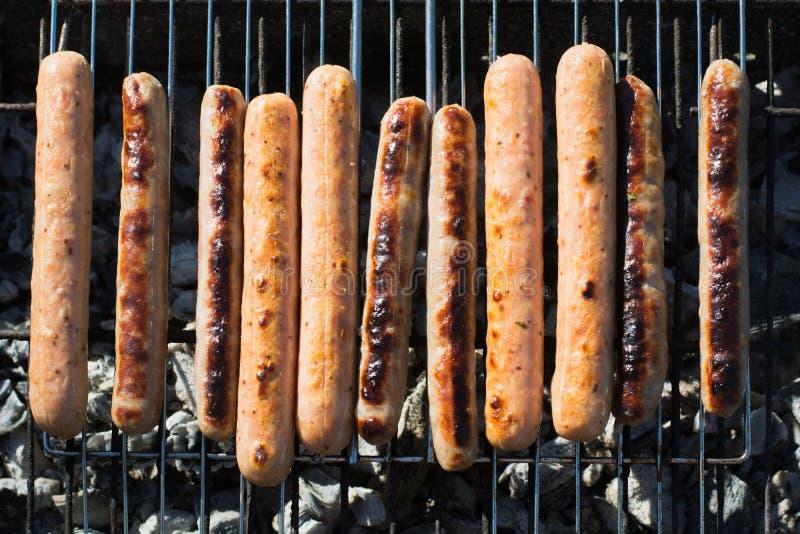 Die würzigen Würste, die auf tragbarem Grill auf Sommer grillen, picknicken draußen Rauch, Feuer Beschneidungspfad eingeschlossen stockbilder