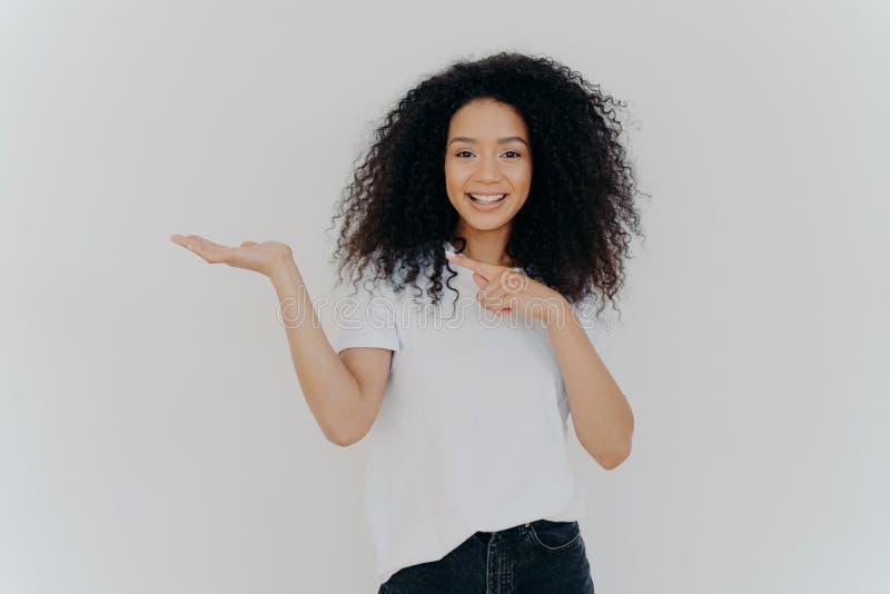 Die Wahl ist einfach Attraktive weibliche Mädchen mit Afro Haare hebt Palme und Punkte auf Leerraum, trifft Entscheidung, hat Zah lizenzfreie stockfotografie