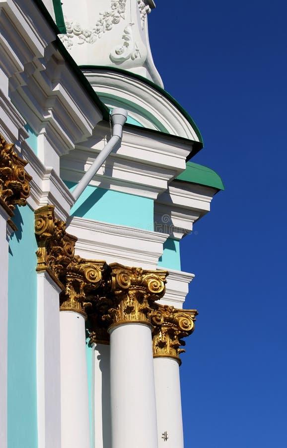 Die Wand der blauen Kirche mit Golddekoration auf den Spalten gegen den blauen Himmel lizenzfreie stockbilder