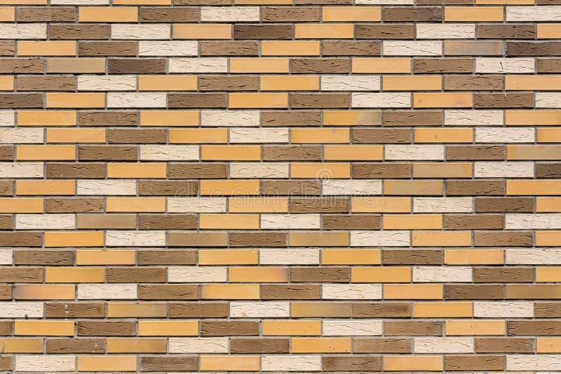 Die Wand des Hauses wird von den bunten dekorativen Ziegelsteinen hergestellt lizenzfreie stockfotografie