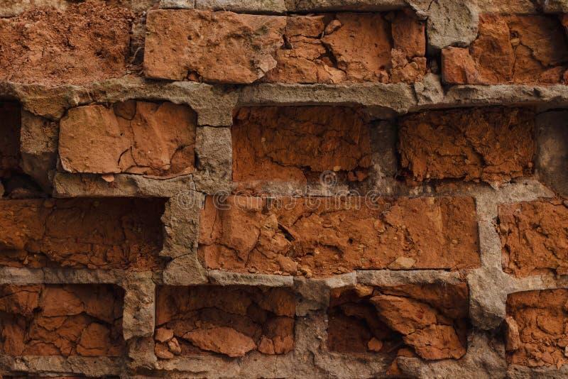 Die Wand des roten verfallenen Ziegelsteines Die ruinierte Backsteinmauernahaufnahme Fassade eines zerstörten Backsteinbaus Muste stockfotografie
