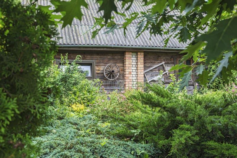 Die Wand eines Dorfhauses mit einem Rad von einem Warenkorb unter dem b stockfotografie