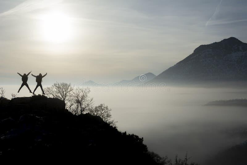 Die Wanderer springend auf Bergspitze lizenzfreie stockbilder
