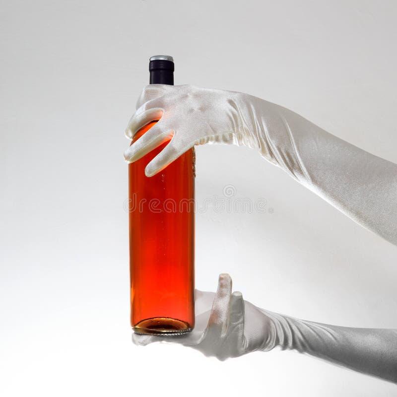 Die weißen Handschuhe der eleganten Frau, die eine Flasche Rotwein lokalisiert auf weißem Hintergrund halten stockfotografie
