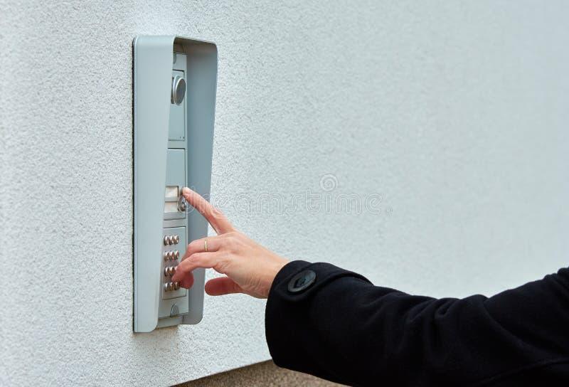 Die weibliche Hand drückt eine Knopftürklingel mit Wechselsprechanlage lizenzfreies stockbild