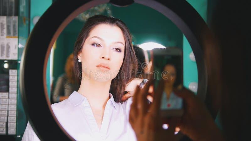 Die weiblichen Hände, die auf dem Smartphone jungen Brunette schießen, modellieren mit Berufsmake-up lizenzfreies stockbild