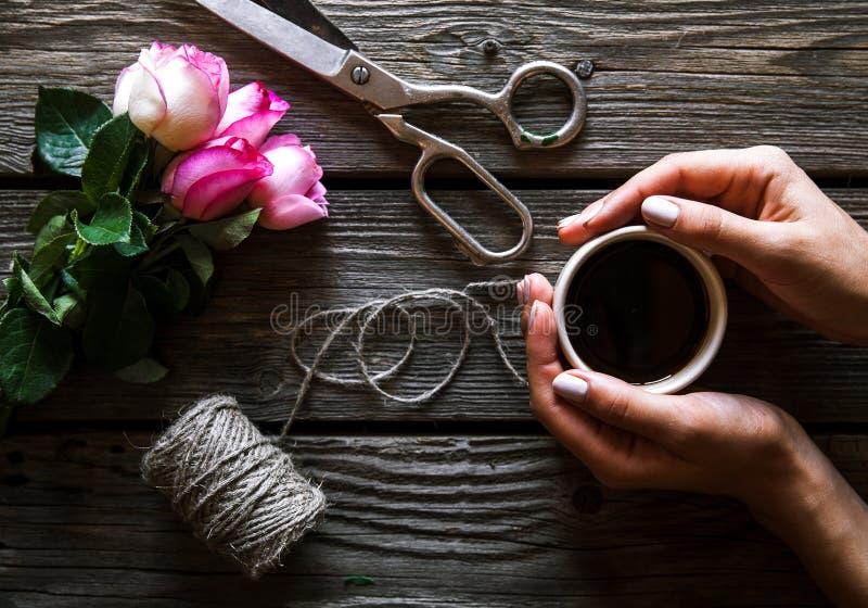 Die weiblichen Hände, die den Blumenstrauß auf Holztisch mit machen, stiegen Blumen stockbild