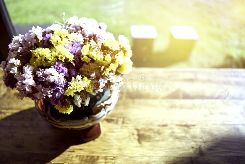 Die Weichzeichnung eines schönen Blumenvase wird auf einen Holztisch in eine Kaffeestube mit einem Glas gelegt lizenzfreies stockbild