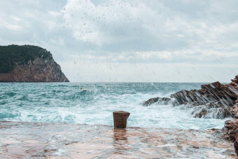 Die Wellen, die auf einem steinigen Strand, einen großen Spray bildend brechen stockbilder