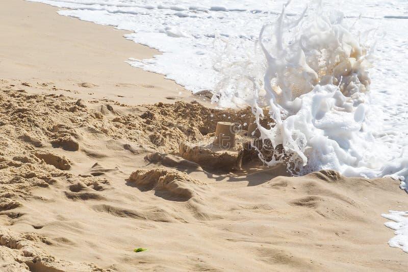 Die Wellen des Ozeans zerstören das Sandburg des Kindes lizenzfreies stockfoto