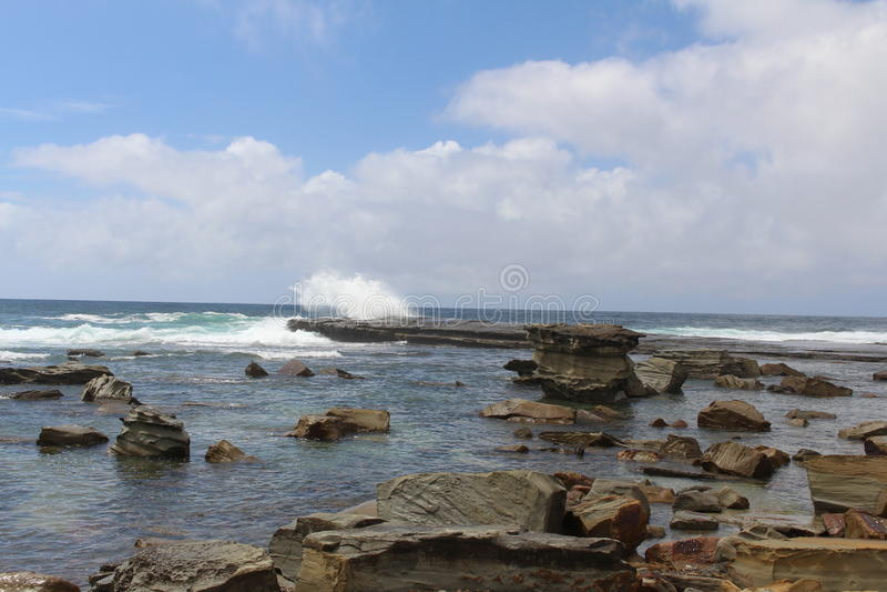 Die Wellen, die auf die Felsen bei Terrigal zerquetschen, setzen auf den Strand stockfotografie
