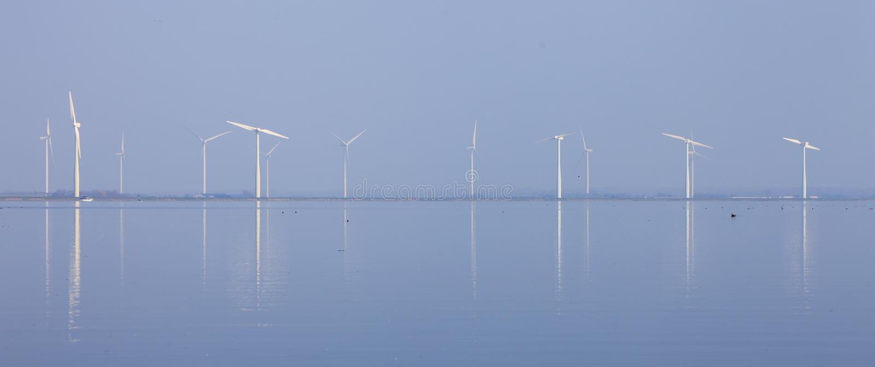 Die Windkraftanlagen und blauer Himmel, die im Wasser von eemmeer nahe reflektiert werden, huizen in Holland lizenzfreie stockfotos