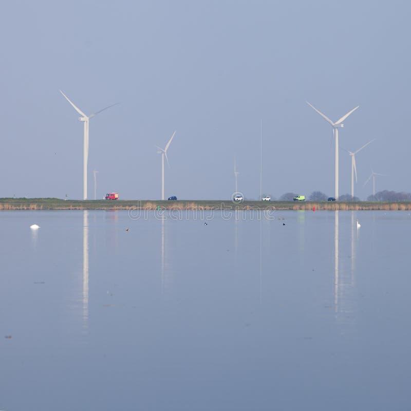 Die Windkraftanlagen und blauer Himmel, die im Wasser von eemmeer nahe reflektiert werden, huizen in Holland stockfotografie