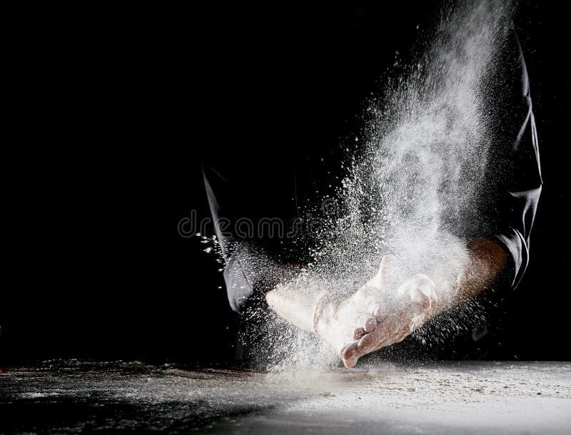 Die Wolke des Mehls sprühend in Luft als Mann reibt Hände lizenzfreie stockfotos
