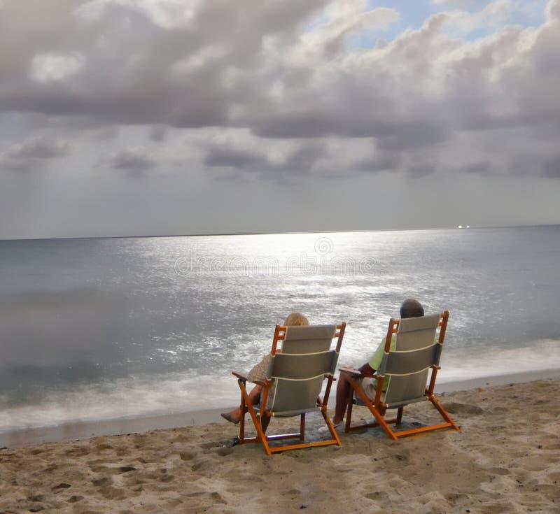 Die Wolken lassen die Vollmondstrahlen zu den Meereswogen eindringen stockfotos