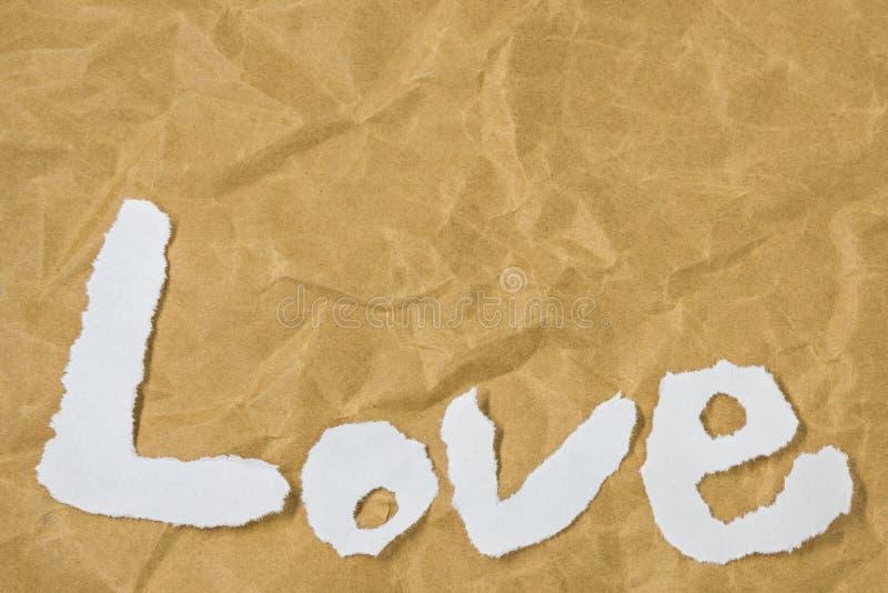 Die Wort Liebe in den herausgeschnittenen Zeitschriftenbuchstaben gesetzt auf braunes Papier stockfotografie