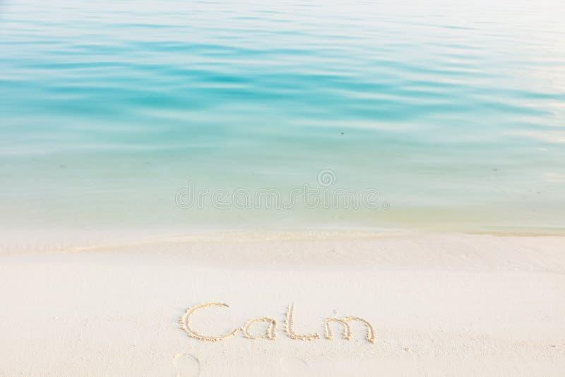Die Wort-Ruhe geschrieben in den Sand auf einen Strand mit blauem Meer-backg stockbilder