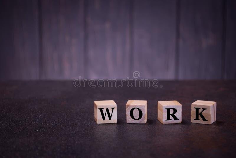 Die Wortarbeit über hölzerne Würfel, auf einem dunklen Hintergrund, helle hölzerne Würfelzeichen, Symbolzeichen stockbild