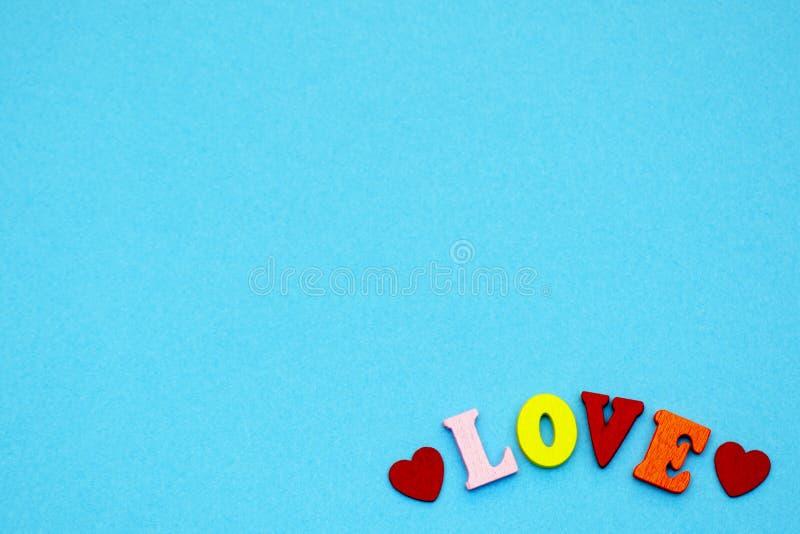 Die Wortliebe und die Herzen auf einem blauen Hintergrund, die Symbole des Feiertag Valentinstags Kopieren Sie Platz lizenzfreie stockfotos