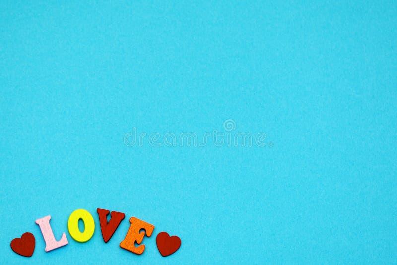 Die Wortliebe und die Herzen auf einem blauen Hintergrund, die Symbole des Feiertag Valentinstags Kopieren Sie Platz stockbild
