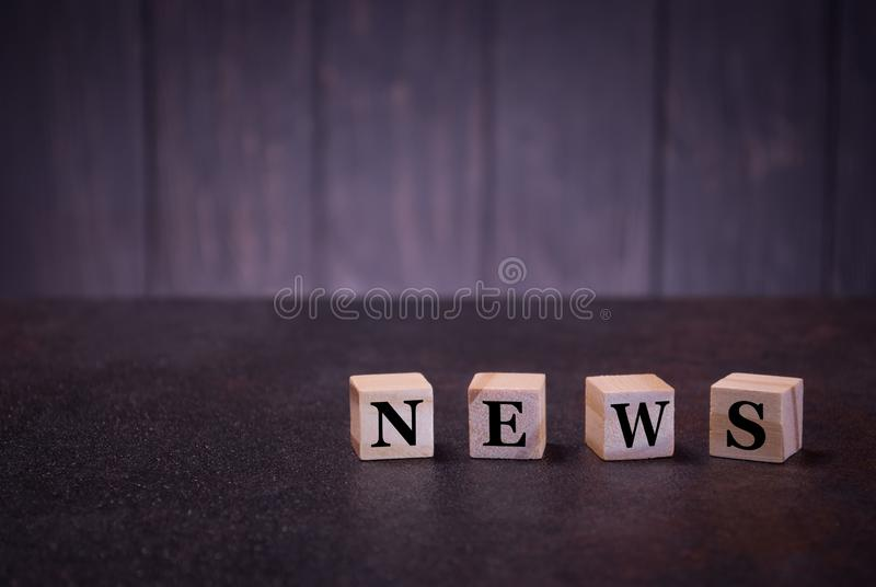 Die Wortnachrichten auf hölzernen Würfeln, auf einem dunklen Hintergrund, helle hölzerne Würfelzeichen, Symbolzeichen lizenzfreie stockfotografie