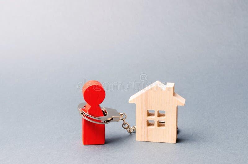 Die Zahl eines Mannes wird zu einem Holzhaus mit Handschellen gefesselt Unmöglichkeit des Zahlens von Zinssätzen auf Hypotheken u lizenzfreie stockfotos