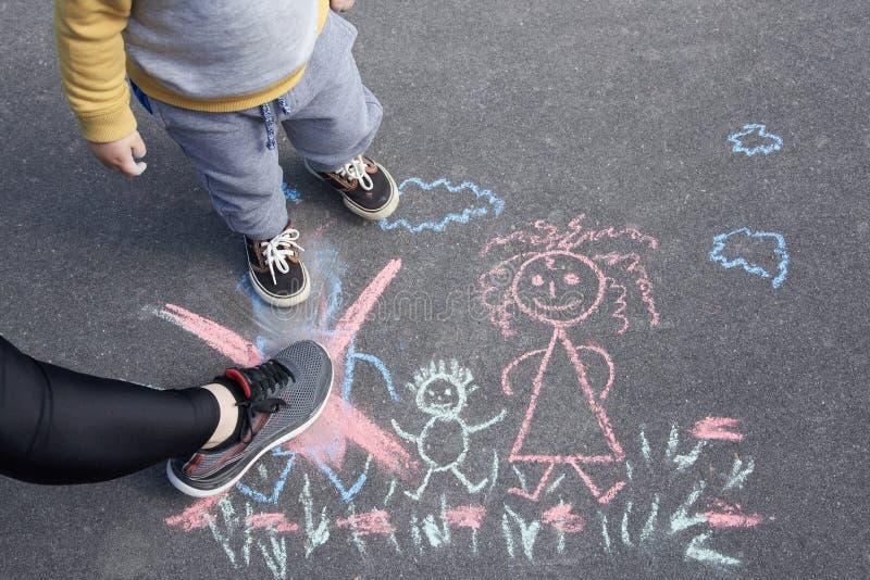 Die Zeichnung der Kinder mit Kreide auf dem Asphalt, Familie ohne Vati Sohn und Mutter kreuzten heraus Vater Familienscheidung lizenzfreie stockfotos