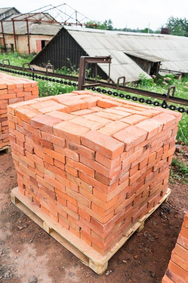 Die Ziegelsteine werden auf hölzernen Paletten gestapelt und vorbereitet für Verkauf Lehmziegelstein ist ein ökologisches Baumate lizenzfreie stockbilder