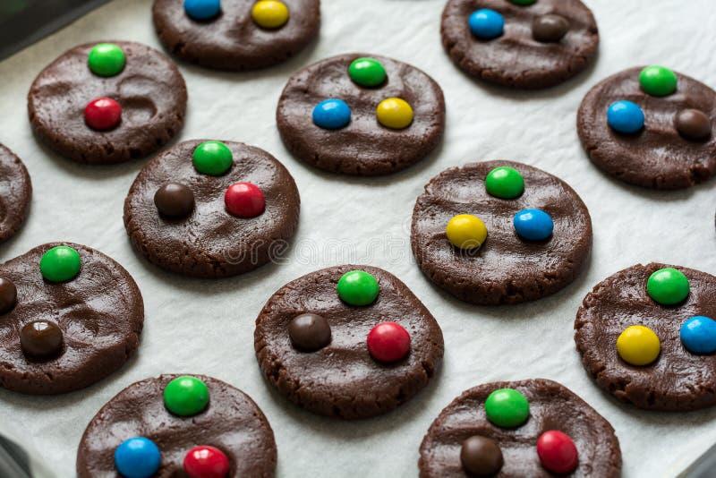 Die Zubereitung von den selbst gemachten Schokoladenplätzchen, die mit farbiger Süßigkeit verziert werden, fällt stockfotografie