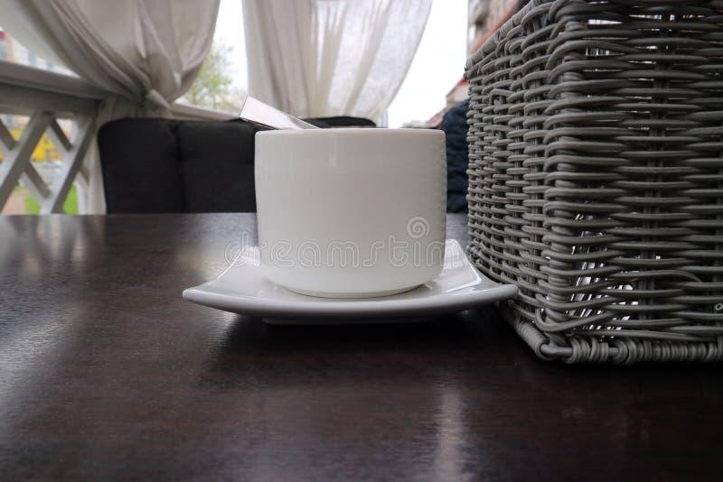 Die Zuckerschüssel steht auf einem Holztisch nahe bei einem Weidenkorb für Geräte als Hintergrund stockfoto