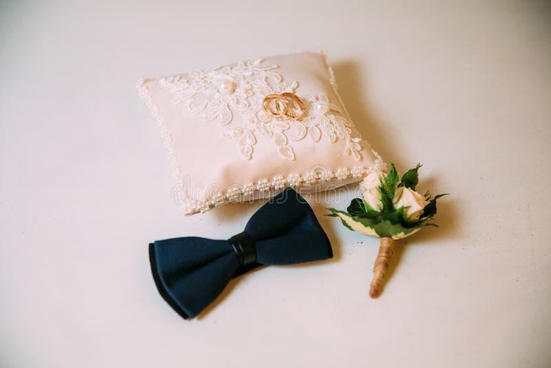 Die Zusätze der Männer, Fliege, heiratende goldene Ringe, Boutonniere auf einer weißen Tabelle Geschäftsmannkleidungs-Detailkonze stockbild