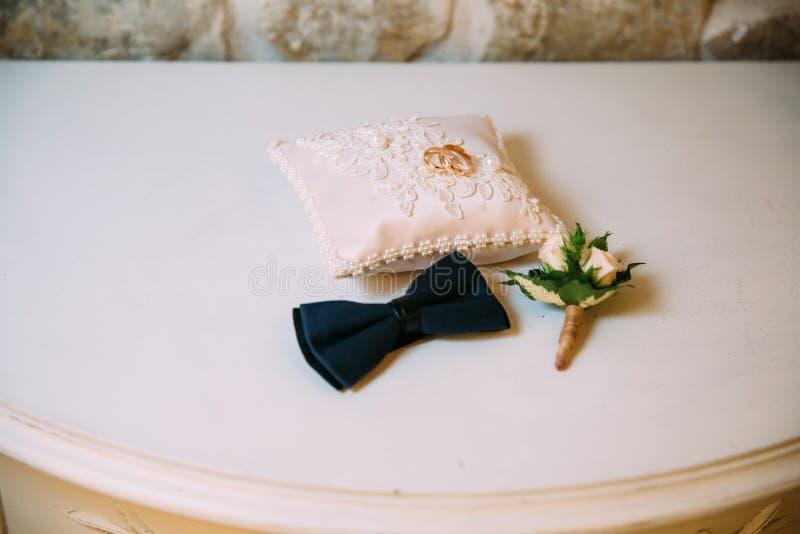 Die Zusätze der Männer, Fliege, heiratende goldene Ringe, Boutonniere auf einer weißen Tabelle Geschäftsmannkleidungs-Detailkonze stockfotografie