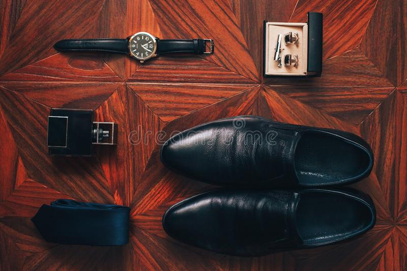 Die Zusätze der Männer: Uhr, Bindung, Gurt, Manschettenknöpfe, Draufsicht der Parfümschuhe stockfoto
