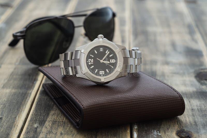 Die Zusätze der Stilllebenmänner mit Uhr, lederner Geldbörse und Sonnenbrille auf altem Schmutzholztisch Stellen Sie von den Zusä stockfoto