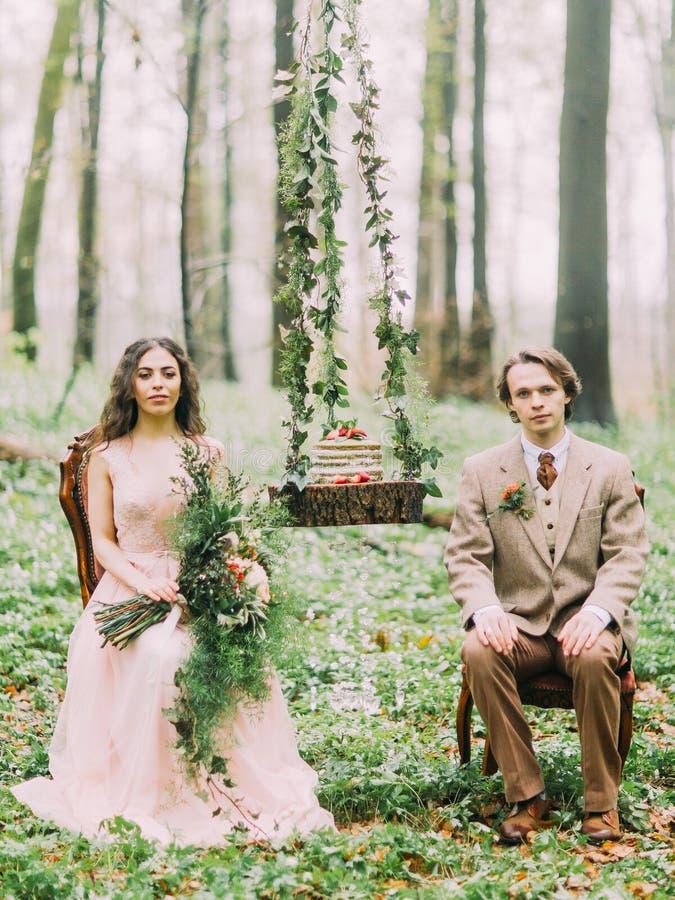 Die Zusammensetzung des Hochzeitsgrünkuchens auf dem Stumpf, der am Baum zwischen den Jungvermähltenpaaren sitzen auf hängt stockfoto