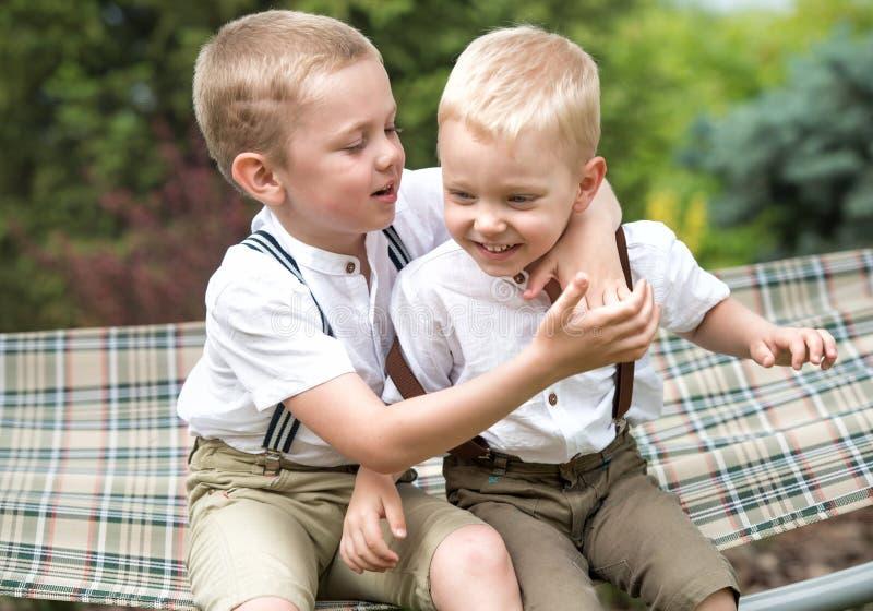 Die zwei Br?der stehen still und sagen Geheimnissen in seinem Ohr Jungenfahrt in der H?ngematte lizenzfreie stockfotos