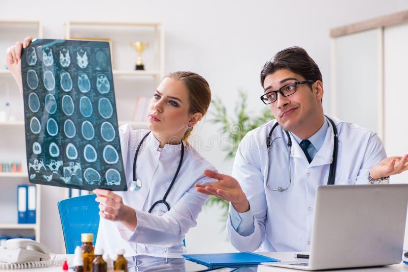 Die zwei Doktoren, die Röntgenstrahlbilder des Patienten für Diagnose überprüfen lizenzfreie stockfotos