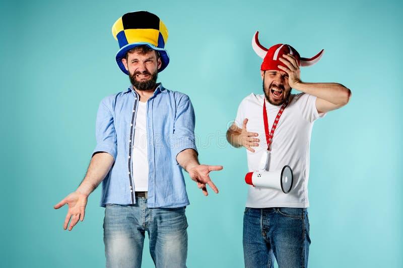 Die zwei Fußballfane mit Mundstück über Blau lizenzfreies stockbild