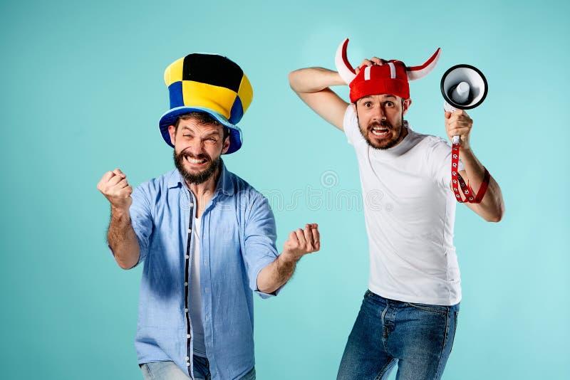 Die zwei Fußballfane mit Mundstück über Blau stockfotografie