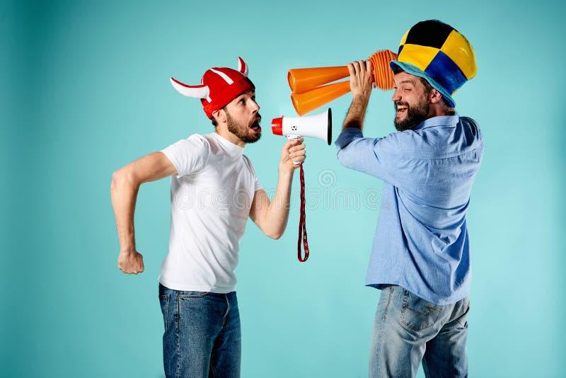Die zwei Fußballfane mit Mundstück über Blau lizenzfreie stockfotos